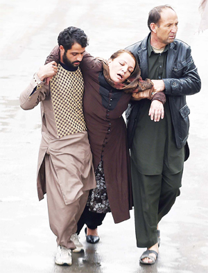 Afghan men assist an injured woman to the Estiqlal Hospital after a massive suicide blast at a Shiite mosque in Kabul on Nov 21. A massive suicide blast at a Shiite mosque in Kabul killed at least 30 people and wounded 35 as worshippers gathered for a religious ceremony, officials said. (AFP)